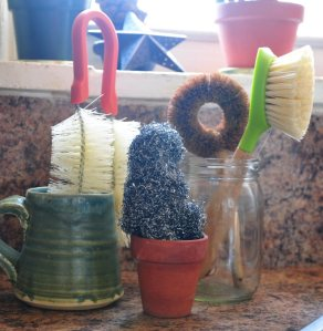 An old mug houses a bottle cleaning brush.  A jar is reused to hold veggie scrub brushes.  A tiny clay pot hold steel wool.